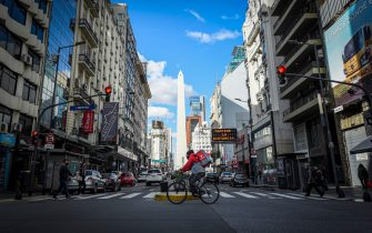 BUENOS AIRES, ARGENTINA - JULY 24: A delivery man crosses the Corrientes avenue known for its traitional pizza places on July 24, 2020 in Buenos Aires, Argentina. Traditional pizza restaurants of the iconic Corrientes Avenue in the Theater District struggle to survive during the government-ordered lockdown to curb spread of COVID-19. Since March 20, they can only work with delivery and take away, which in most cases represents a significant drop in their sales. Unable to adapt or be profitable, some pizzerias opted to remain closed until situation comes back to normal while others had to close down definitively. (Photo by Marcelo Endelli/Getty Images)