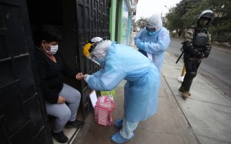 LIMA, PERU - JULY 21: Doctors escorted by a soldier take a rapid test during a house-to-house coronavirus testing drive on July 21, 2020 in Lima, Peru. Medical staff visit different areas of Lima and test citizens of high-risk groups. Peru was the first country to impose widespread quarantine on March 16. To date, reports over 13,187 deaths and 353,590 positive cases of COVID-19. (Photo by Raul Sifuentes/Getty Images)