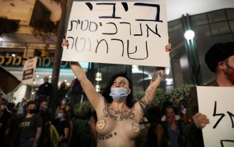 epa08566225 A half naked protester wearing only Netanyahu's face on her chest holds a placard in Hebrew containing profanity against PM Netanyahu, during a protest against Israeli Prime Minister Benjamin Netanyahu corruption charges, outside his residence in Jerusalem, Israel, 25 July 2020. Netanyahu face an ongoing trial with indictments filed against him by the State Attorney's Office on a charges of fraud, bribery, and breach of trust.  EPA/ABIR SULTAN