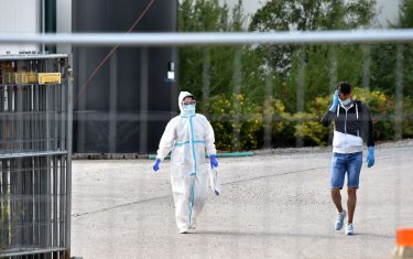 A member of a medical team wearing protective clothes walks inside a farming compound in Mamming, southern Germany, on July 27, 2020 where an outbreak an outbreak of COVID-10 coronavirus cases among seasonal workers has occured. - At least 174 seasonal workers have tested positive for the virus on the farm in the municipality of Mamming, most of them from Hungary, Romania, Bulgaria and Ukraine, and some 500 workers were sent into quarantine on the Bavarian farm at the weekend to contain a mass coronavirus outbreak. (Photo by Christof STACHE / AFP) (Photo by CHRISTOF STACHE/AFP via Getty Images)