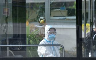 A member of a medical team wearing protective clothes stands behind a parked bus at an accommodation of seasonal workers of a farm in Mamming, southern Germany, on July 27, 2020 where an outbreak an outbreak of COVID-10 coronavirus cases among seasonal workers has occured. - At least 174 seasonal workers have tested positive for the virus on the farm in the municipality of Mamming, most of them from Hungary, Romania, Bulgaria and Ukraine, and some 500 workers were sent into quarantine on the Bavarian farm at the weekend to contain a mass coronavirus outbreak. (Photo by Christof STACHE / AFP) (Photo by CHRISTOF STACHE/AFP via Getty Images)