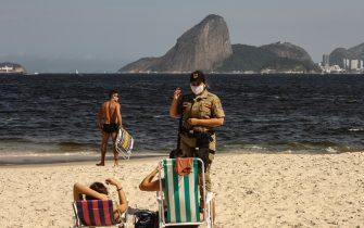 NITEROI, BRAZIL - JULY 26: A police officer asks beach goers to leave at Icarai Beach amidst the coronavirus (COVID-19) pandemic on July 26, 2020 in Niteroi, Brazil. The practice of physical activities on boardwalks and individual sports at sea is allowed. However, the use of chairs and tents on the sand is still prohibited. Starting next week group sports such as volleyball and football can be practiced, but only on weekdays. (Photo by Luis Alvarenga/Getty Images)