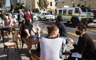 People working in the restaurant, food and alcohol industry, sit at tables that a restaurant placed on a traffic island, to take part in a nationwide protest against provisions in South African government Lockdown legislation, which threatens the survival of the businesses and jobs, in Cape Town city centre, on July 22, 2020. - The reintroduction on the ban on alcohol sales and a night curfew by the South African government will have a negative economic impact on the hospitality industry. (Photo by RODGER BOSCH / AFP) (Photo by RODGER BOSCH/AFP via Getty Images)