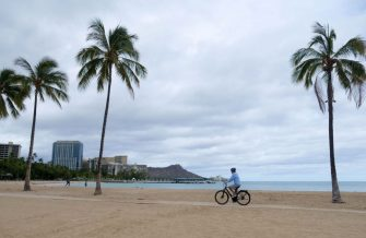 A cyclist rides along an empty Waikiki Beach as Hurricane Douglas veers northward sparing Oahu from a direct hit, in Honolulu, Hawaii, on July 26, 2020. - Pacific Hurricane Douglas -- was bearing down on the Hawaiian islands Sunday and was expected to move over parts of the state later in the day and on Monday. A hurricane warning was in effect for Maui and Kauai counties, as well as Oahu -- the island on which Honolulu, a city of just under 350,000 -- is located. (Photo by Ronen ZILBERMAN / AFP) (Photo by RONEN ZILBERMAN/AFP via Getty Images)