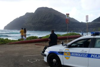 Police wait for people to return to their cars before closing the beach parking lot in preparation for Hurricane Douglas, in Honolulu, Hawaii, on July 26, 2020. - Pacific Hurricane Douglas -- was bearing down on the Hawaiian islands Sunday and was expected to move over parts of the state later in the day and on Monday. A hurricane warning was in effect for Maui and Kauai counties, as well as Oahu -- the island on which Honolulu, a city of just under 350,000 -- is located. (Photo by Ronen ZILBERMAN / AFP) (Photo by RONEN ZILBERMAN/AFP via Getty Images)