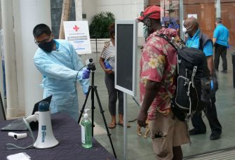 Medical volunteers take temperature readings on people arriving to shelter at the Hawaii Convention Center seeking a safe place to weather Hurricane Douglas in Honolulu, Hawaii, on July 26, 2020. - Pacific Hurricane Douglas -- was bearing down on the Hawaiian islands Sunday and was expected to move over parts of the state later in the day and on Monday. A hurricane warning was in effect for Maui and Kauai counties, as well as Oahu -- the island on which Honolulu, a city of just under 350,000 -- is located. (Photo by Ronen ZILBERMAN / AFP) (Photo by RONEN ZILBERMAN/AFP via Getty Images)