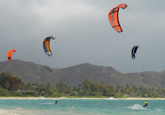 Kite surfers enjoy increasing winds ahead of Hurricane Douglas in the windward town of Kailua on the island of Oahu, Hawaii on July 26, 2020. - Pacific Hurricane Douglas -- was bearing down on the Hawaiian islands Sunday and was expected to move over parts of the state later in the day and on Monday. A hurricane warning was in effect for Maui and Kauai counties, as well as Oahu -- the island on which Honolulu, a city of just under 350,000 -- is located. (Photo by Ronen ZILBERMAN / AFP) (Photo by RONEN ZILBERMAN/AFP via Getty Images)