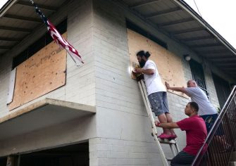(From L) Mapu Obrien, Jack Obrien, and Masta Obrien board up the windows of their home in preparation for hurricane Douglas in Honolulu, Hawaii, on July 25, 2020. - Douglas is expected to be a category 1 hurricane with winds 74 to 95mph (119 to 152kph), as it approaches the islands this weekend. (Photo by Ronen Zilberman / AFP) (Photo by RONEN ZILBERMAN/AFP via Getty Images)