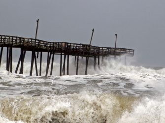 """TOPSHOT - Waves crash on Rodanthe Pier as Hurricane Dorian hits Cape Hatteras in North Carolina on September 6, 2019. - The final death toll from Hurricane Dorian in the Bahamas could be """"staggering,"""" a government minister has said as the storm lashed North Carolina in the US Friday with torrential rain and fierce wind. (Photo by Jose Luis Magana / AFP) (Photo by JOSE LUIS MAGANA/AFP via Getty Images)"""
