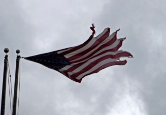 """An American flag is seen in Rodanthe as Hurricane Dorian hits Cape Hatteras in North Carolina. on September 6, 2019. - The final death toll from Hurricane Dorian in the Bahamas could be """"staggering,"""" a government minister has said as the storm lashed North Carolina in the US Friday with torrential rain and fierce wind. (Photo by Jose Luis Magana / AFP) (Photo by JOSE LUIS MAGANA/AFP via Getty Images)"""