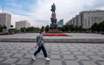 A woman wearing a face mask to protect against the coronavirus disease walks in front of a monument to the Soviet Union founder Vladimir Lenin in Moscow on July 27, 2020. (Photo by Yuri KADOBNOV / AFP) (Photo by YURI KADOBNOV/AFP via Getty Images)