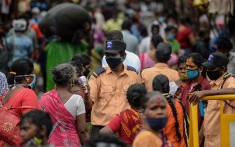 A security personnel (C) checks the body temperature of a woman (C-L) as she enters a market among a crowd of people as a preventive measure against the spread of the COVID-19 coronavirus in Chennai on July 29, 2020. (Photo by Arun SANKAR / AFP) (Photo by ARUN SANKAR/AFP via Getty Images)