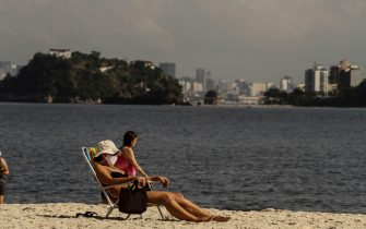 NITEROI, BRAZIL - JULY 26: A woman wearing a face mask enjoys the weather at Icarai Beach amidst the coronavirus (COVID-19) pandemic on July 26, 2020 in Niteroi, Brazil. The practice of physical activities on boardwalks and individual sports at sea is allowed. However, the use of chairs and tents on the sand is still prohibited. Starting next week group sports such as volleyball and football can be practiced, but only on weekdays. (Photo by Luis Alvarenga/Getty Images)