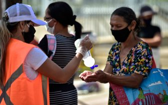 BELO HORIZONTE, BRAZIL - JUNE 05: A woman receives hand sanitizer while waiting in line to receive lunch at Praça da Estação on June 5, 2020 in Belo Horizonte, Brazil. About 3000 meals are being distributed every Friday, in addition to food, fruit and water. The campaign is carried out by a bank credit company in Belo Horizonte. (Photo by Pedro Vilela/Getty Images)