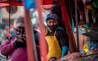 Street vendors wear facemasks as a preventive measure against the spread of the novel coronavirus, COVID-19, in Corabastos square in the Kennedy neighborhood of Bogota on July 28, 2020. - Recorded deaths from the coronavirus neared 650,000 on July 27 as the disease surged back at hotspots in Asia, Europe and the Americas, prompting renewed restrictions, targeted lockdowns and compulsory mask-wearing orders. (Photo by Juan BARRETO / AFP) (Photo by JUAN BARRETO/AFP via Getty Images)