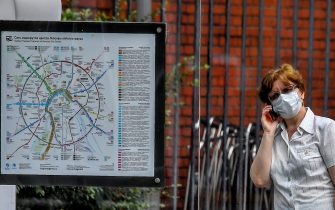 A woman wearing a face mask to protect against the coronavirus disease speaks on a mobile phone while walking past a Moscow transport map on July 27, 2020. (Photo by Yuri KADOBNOV / AFP) (Photo by YURI KADOBNOV/AFP via Getty Images)