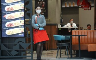 MOSCOW, RUSSIA - JULY 18: A waitress wearing a protective face mask stands at the entrance of a restaurant at the Metropolis mall, on July 18, 2020 in Moscow, Russia. The requirement to wear masks and gloves to combat a spread of the coronavirus (COVID-19) is still in effect in Moscow's region. (Photo by Mikhail Svetlov/Getty Images)