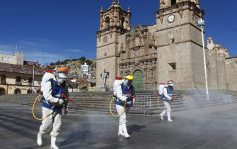 Health workers disinfect the main Plaza of Puno, Peru on June 18, 2020, amid the COVID-19 coronavirus pandemic. - Peru surpassed 240,000 cases of coronavirus and moved to second behind Brazil in Latin America and seventh among the countries in the world with the highest number of infections surpassing Italy, the Ministry of Health reported. (Photo by Carlos MAMANI / AFP) (Photo by CARLOS MAMANI/AFP via Getty Images)