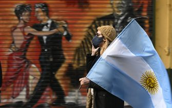 A woman holds an Argentine flag during a protest against Argentina's President Alberto Fernandez health policies within the tight virus lockdown measures against the spread of the novel COVID-19 coronavirus, at Republica square in Buenos Aires, Argentina, on July 9, 2020. (Photo by JUAN MABROMATA / AFP) (Photo by JUAN MABROMATA/AFP via Getty Images)