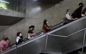 epa08570683 A group of people climb an escalator, in Sao Paulo, Brazil, 28 July 2020. To date, Brazil is close to 90 thousand deaths from the coronavirus.  EPA/Fernando Bizerra