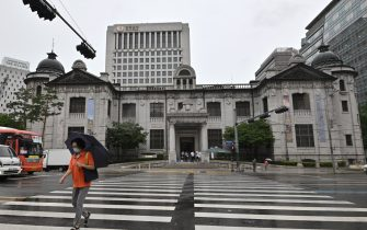 A woman crosses the road in front of the Bank of Korea in Seoul on July 23, 2020. - South Korea's economy recorded its worst performance in more than 20 years in the second quarter, the central bank said on July 23, as the coronavirus pandemic hammered its exports. (Photo by Jung Yeon-je / AFP) (Photo by JUNG YEON-JE/AFP via Getty Images)