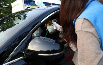 SEOUL, SOUTH KOREA - JULY 17: A event staff checks the temperature of audience while enter at a drive-in concert as South Koreans take measures to protect themselves against the spread of coronavirus (COVID-19) on July 17, 2020 in Seoul, South Korea. South Korea's new daily virus cases came in at around 60 for the second straight day on Friday as the country grapple with rising imported cases and an uptick in local infections. The country added 60 cases tody, including 21 local infections, raising the total caseload to 13,672, according to the Korea Centers for Disease Control and Prevention (KCDC). (Photo by Chung Sung-Jun/Getty Images)