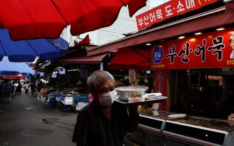 SEOUL, SOUTH KOREA - JULY 21: A South Korean man wears a mask to prevent the coronavirus holds a dining table in the Namdaemun market on July 21, 2020 in Seoul, South Korea. With the number of daily local cases recently hovering around 20 or below, but imported cases continued to rise by double digit figures. South Korea resumed operations of some museums and libraries in the greater Seoul area starting yeaterday. Health authorities, however, are still vigilant over the spread of the virus in vacation spots over the summer, pointing out that the season will serve as a critical juncture for the nation's anti-virus fight. The country added 45 cases toddy, including 20 local infections, raising the total caseload to 13,816, according to the Korea Centers for Disease Control and Prevention (KCDC). (Photo by Chung Sung-Jun/Getty Images)
