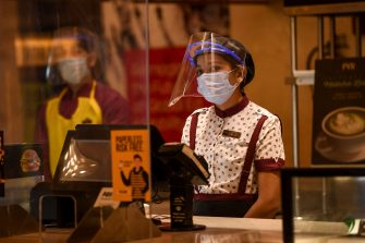 PVR Cinemas employees wearing face shields, gloves and facemasks, participate in a sanitisation work as part of preparations for a possible reopening amid concerns over the spread of the COVID-19 coronavirus, in New Delhi on July 31, 2020. (Photo by Prakash SINGH / AFP) (Photo by PRAKASH SINGH/AFP via Getty Images)