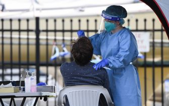 SYDNEY, AUSTRALIA - AUGUST 02: A healthcare worker wearing a face shield and protective clothing tests a man for COVID-19 at a pop-up testing clinic in Rushcutters Bay on August 02, 2020 in Sydney, Australia. As Sydney COVID-19 clusters in the east, inner west and south west continue to grow, Sydney is on high alert with a further 12 cases of COVID-19 reported overnight in New South Wales. (Photo by James D. Morgan/Getty Images)