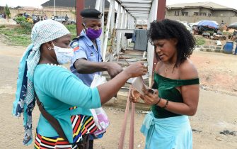 A policeman instructs a lady to wear face mask at a checkpoint in compliance with state directive to curb the spread of COVID-19 coronavirus at Ojodu-Berger in Lagos, on May 4, 2020. - Kano, with around 12 million people, is the second most populous state in Nigeria. The Nigeria Centre for Disease Control on May 1, 2020, said the number of recorded infections across Kano rose to 219, up from 77 at the start of the week.Kano has in recent days seen a spate of high-profile deaths including academics, bureaucrats, businessmen and traditional leaders. (Photo by PIUS UTOMI EKPEI / AFP) (Photo by PIUS UTOMI EKPEI/AFP via Getty Images)