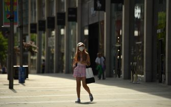 """A pedestrian wearing a facemask is seen in the centre of Manchester, northwest England, on July 31, 2020. - Britain on Friday """"put the brakes on"""" easing lockdown measures and imposed new rules on millions of households in northern England, following concerns over a spike in coronavirus infections. (Photo by Oli SCARFF / AFP) (Photo by OLI SCARFF/AFP via Getty Images)"""
