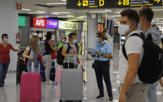 MALLORCA, SPAIN - JULY 30: TUI workers speak to passengers at arrivals in Palma de Mallorca airport on July 30, 2020 in Mallorca, Spain. The United Kingdom, whose citizens comprise the largest share of foreign tourists in Spain, added Mallorca and other Spanish islands to its advice against non-essential travel to the country, citing a rise in coronavirus cases. The change follows the UK's decision to reimpose a 14-day isolation period for travelers returning from Spain. (Photo by Clara Margais/Getty Images)