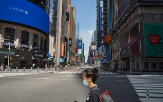 NEW YORK, NEW YORK - AUGUST 01: Times Square appears empty as a person wearing a protective face mask crosses a street during Phase 4 of re-opening following restrictions imposed to curb the coronavirus pandemic on August 1, 2020 in New York, New York. The fourth phase allows outdoor arts and entertainment, sporting events without fans and media production. (Photo by Rob Kim/Getty Images)