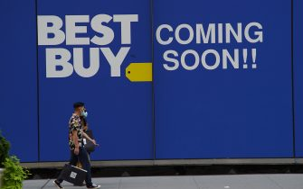 NEW YORK, NEW YORK - AUGUST 01: People walk by a Best Buy store during Phase 4 of re-opening following restrictions imposed to curb the coronavirus pandemic on August 1, 2020 in New York, New York. The fourth phase allows outdoor arts and entertainment, sporting events without fans and media production. (Photo by Rob Kim/Getty Images)
