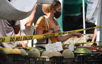 A woman wearing a face covering shops for melons at the Santa Monica Farmers' Market in Santa Monica, California, August 1, 2020 during the coronavirus pandemic. - The scale of economic devastation from the pandemic was laid bare on July 30 as Western economies recorded historic slumps, just as resurgent caseloads forced many countries into agonising new trade-offs between health and financial stability. (Photo by Robyn Beck / AFP) (Photo by ROBYN BECK/AFP via Getty Images)