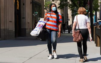 NEW YORK, NEW YORK - AUGUST 01:  A woman walks while wearing a protective mask as the city continues Phase 4 of re-opening following restrictions imposed to slow the spread of coronavirus on August 1, 2020 in New York City. The fourth phase allows outdoor arts and entertainment, sporting events without fans and media production. (Photo by Cindy Ord/Getty Images)
