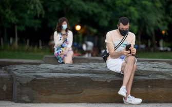 NEW YORK, NEW YORK - AUGUST 01: A man wearing a mask looks at his phone while sitting along the Hudson River Greenway near the Chelsea Piers as the city continues Phase 4 of re-opening following restrictions imposed to slow the spread of coronavirus on August 01, 2020 in New York City. The fourth phase allows outdoor arts and entertainment, sporting events without fans and media production. (Photo by Alexi Rosenfeld/Getty Images)