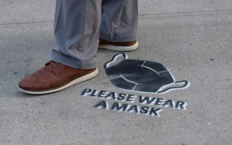 NEW YORK, NEW YORK - AUGUST 01: A person is seen standing near a 'please wear a mask' sign painted on the sidewalk in Chelsea as the city continues Phase 4 of re-opening following restrictions imposed to slow the spread of coronavirus on August 01, 2020 in New York City. The fourth phase allows outdoor arts and entertainment, sporting events without fans and media production. (Photo by Alexi Rosenfeld/Getty Images)