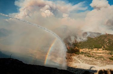 Water from a fire engine creates a rainbow near flames as firefighters continue to battle the Apple fire near Banning, California on August 1, 2020. - 4,125 acres have burn in Cherry Valley, about 2,000 people have received evacuation orders in the afternoon of August 1.  Around 8PM the fire spread to 12,000 acres. (Photo by JOSH EDELSON / AFP) (Photo by JOSH EDELSON/AFP via Getty Images)