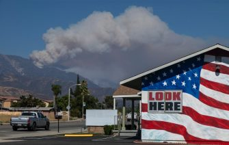 CHERRY VALLEY, CA - AUGUST 02: Smoke from the Apple Fire is seen behind a stars and stripes painted building in the community of Calimesa on August 2, 2020 near Cherry Valley, California. The wildfire has spread across more than 20,000 acres and forced 7,000 residents from their homes.  (Photo by David McNew/Getty Images)