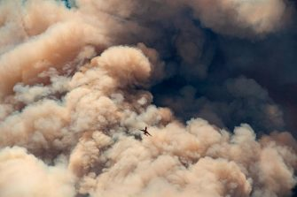 A firefighting airplane flies away from a pyrocumulus ash plume after making a retardant drop on a ridge as firefighters continue to battle the Apple fire near Banning, California on August 1, 2020. - 4,125 acres have burn in Cherry Valley, about 2,000 people have received evacuation orders in the afternoon of August 1. (Photo by JOSH EDELSON / AFP) (Photo by JOSH EDELSON/AFP via Getty Images)