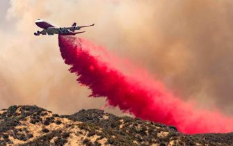 TOPSHOT - The 747 Supertanker makes a retardant drop on a ridge as firefighters continue to battle the Apple fire near Banning, California on August 1, 2020. - 4,125 acres have burn in Cherry Valley, about 2,000 people have received evacuation orders in the afternoon of August 1. (Photo by JOSH EDELSON / AFP) (Photo by JOSH EDELSON/AFP via Getty Images)