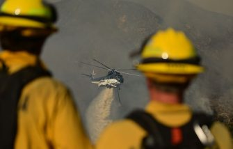 A helicopter drops water on hot spots during the Apple fire near Banning, California on August 1, 2020. - 4,125 acres have burn in Cherry Valley, about 2,000 people have received evacuation orders in the afternoon of August 1.  Around 8PM the fire spread to 12,000 acres. (Photo by JOSH EDELSON / AFP) (Photo by JOSH EDELSON/AFP via Getty Images)