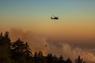 CHERRY VALLEY, CA - AUGUST 01: A helicopter drops water on the Apple Fire as an excessive heat warning continues on August 1, 2020 in Cherry Valley, California. The fire began shortly before 5 p.m. the previous evening, threatening a large number of homes overnight and forcing thousands to flee before exploding to 12,000 acres this afternoon, mostly climbing the steep wilderness slopes of the San Bernardino Mountains.  (Photo by David McNew/Getty Images)