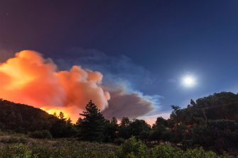 CHERRY VALLEY, CA - AUGUST 01: Flames approach on a western front of the Apple Fire, consuming brush and forest under a nearly full moon during an excessive heat warning on August 1, 2020 in Cherry Valley, California. The fire began shortly before 5 p.m. the previous evening, threatening a large number of homes overnight and forcing thousands to flee before exploding to 12,000 acres this afternoon, mostly climbing the steep wilderness slopes of the San Bernardino Mountains.  (Photo by David McNew/Getty Images)
