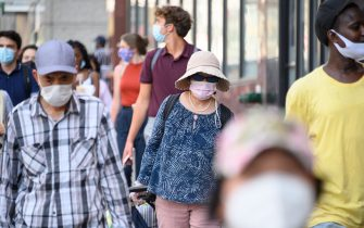 NEW YORK, NEW YORK - AUGUST 03: People wear protective face masks in Chinatown as the city continues Phase 4 of re-opening following restrictions imposed to slow the spread of coronavirus on August 3, 2020 in New York City. The fourth phase allows outdoor arts and entertainment, sporting events without fans and media production. (Photo by Noam Galai/Getty Images)