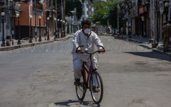 SRINAGAR,KASHMIR INDIA - AUGUST 04: A Kashmiri man covering his face with a protective mask paddles his bicycle on a deserted road in the city center during a curfew on August 04, 2020  in Srinagar, the summer capital of Indian administered Kashmir, India. Indian police and paramilitary personnel were deployed in strength as authorities imposed a curfew in summer capital city Srinagar due to apprehensions of anti-India protests on the first anniversary of the Indian government stripping the Himalayan region, contested by both India and Pakistan since 1947, of its autonomy and downgrading its status from a state to a union  territory in a stealth move last year. The region is already reeling under a lockdown imposed by authorities to curb the spread of coronavirus. (Photo by Yawar Nazir/Getty Images)