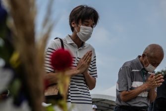 HIROSHIMA, JAPAN - AUGUST 06: People pray in remembrance during the 75th anniversary of the Hiroshima atomic bombing, on August 6, 2020 in Hiroshima, Japan. In a ceremony that has been scaled back significantly because of Covid-19 coronavirus, Japan will mark the 75th anniversary of the first atomic bomb that was dropped by the United States on Hiroshima on August 6, 1945. The bomb instantly killed an estimated 70,000 people and thousands more in coming years from radiation effects. Three days later the United States dropped a second atomic bomb on Nagasaki which ended World War II. (Photo by Carl Court/Getty Images)