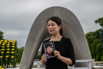 HIROSHIMA, JAPAN - AUGUST 06: A woman holds a photograph of her grandfather who survived the Hiroshima atomic bomb as she has her photograph taken by a relative next to the Victims Memorial Cenotaph during the 75th anniversary of the Hiroshima atomic bombing, on August 6, 2020 in Hiroshima, Japan. In a ceremony that has been scaled back significantly because of Covid-19 coronavirus, Japan will mark the 75th anniversary of the first atomic bomb that was dropped by the United States on Hiroshima on August 6, 1945. The bomb instantly killed an estimated 70,000 people and thousands more in coming years from radiation effects. Three days later the United States dropped a second atomic bomb on Nagasaki which ended World War II. (Photo by Carl Court/Getty Images)