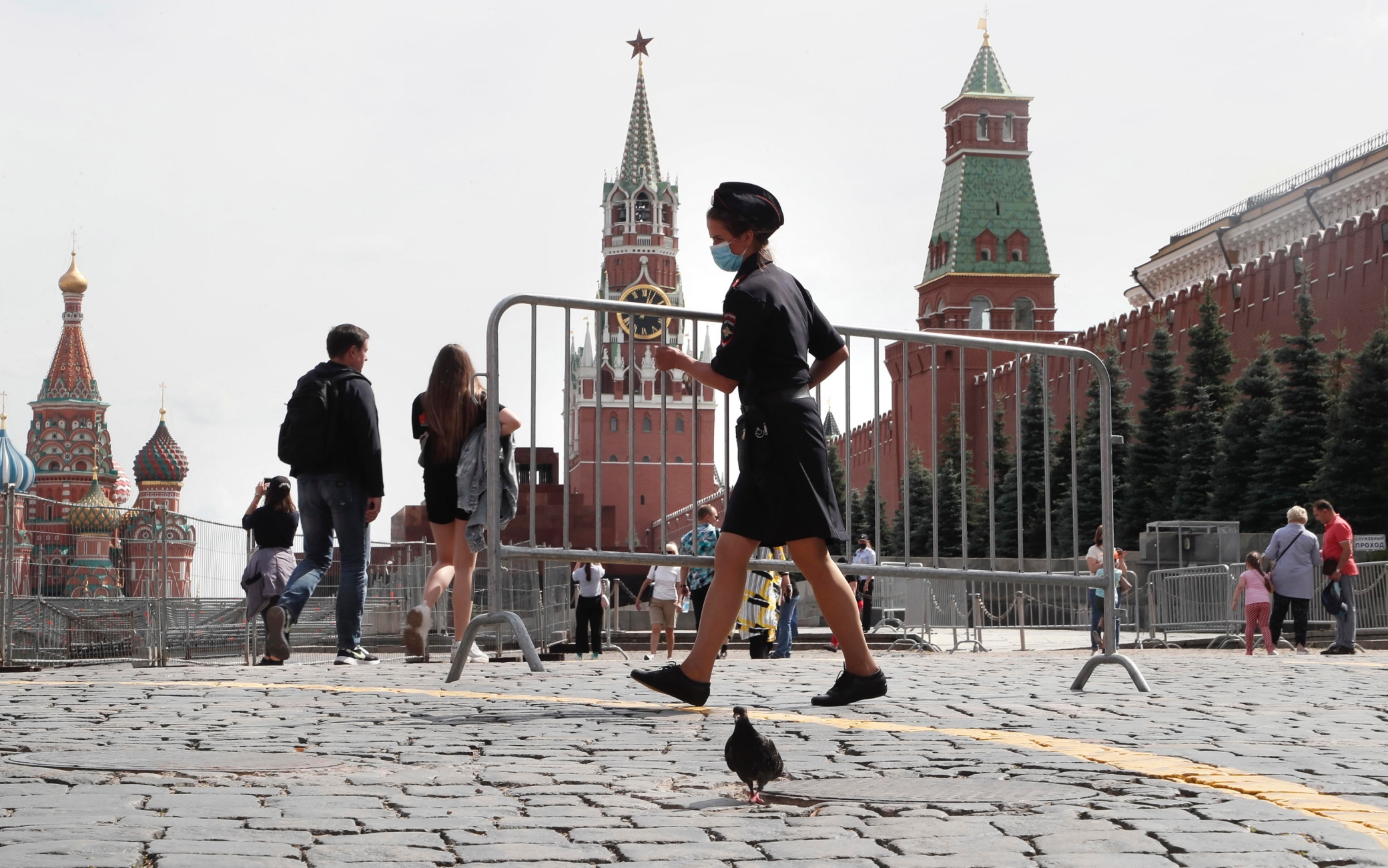 epa08583404 A female police officer wearing a protective face mask moves a temporary fencing on the Red Square in Moscow, Russia, 04 August 2020. Russian authorities continue to gradually ease restrictions imposed to prevent the spread of the pandemic COVID-19 disease caused by the SARS-CoV-2 coronavirus in the country.  EPA/MAXIM SHIPENKOV
